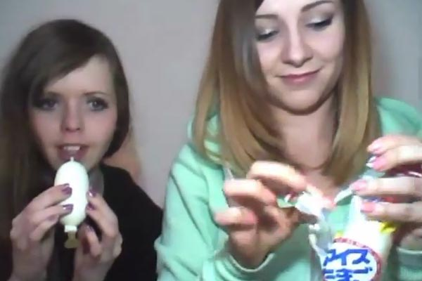 Two girls eat ice cream from a condom