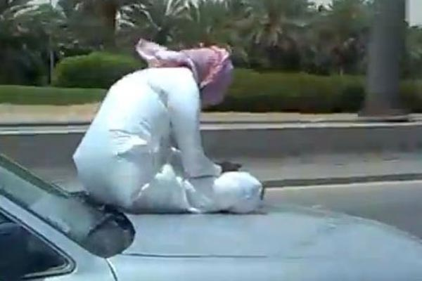 Saudi man texting on hood of car